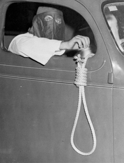 In this May 3, 1939 file photo, a noose dangles from an automobile carrying Ku Klux Klan members, warning blacks to stay away from polling places for a municipal primary election in Miami. In spite of the threats, over 600 black voters cast their ballots. (AP Photo/File)
