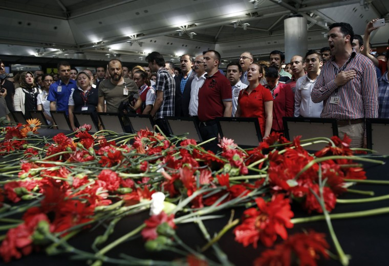 Family members, colleagues and friends of the victims of Tuesday blasts gather for a memorial ceremony at the Ataturk Airport in Istanbul, Thursday, June 30, 2016. A senior Turkish official on Thursday identified the nationalities of Istanbul airport attackers after police carried out raids looking for Islamic State suspects. Tuesday's gunfire and suicide bombing attack at Ataturk Airport killed dozens and injured over 200. Turkish authorities have banned distribution of images relating to the Ataturk airport attack within Turkey. (AP Photo/Emrah Gurel)