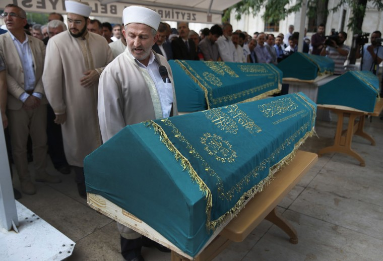 An imam offers prayers in front of the coffins of four members of the Amiri family, killed Tuesday at the blasts in Istanbul's Ataturk airport, during the funeral in Istanbul, Thursday, June 30, 2016. Suicide attackers killed dozens and wounded scores of others at the busy airport late Tuesday, the latest in a series of bombings to strike Turkey in recent months. Turkish authorities have banned distribution of images relating to the Ataturk airport attack within Turkey. (AP Photo/Lefteris Pitarakis)