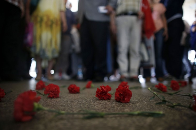 Colleagues leave carnations for Erol Eskisoy and Ali Zulfukar Yorulmaz, two taxi drivers killed in Tuesday's blasts at the entrance of Ataturk Airport in Istanbul, Thursday, June 30, 2016. A senior Turkish official on Thursday identified the Istanbul airport attackers as a Russian, Uzbek and Kyrgyz national hours after police carried out sweeping raids across the city looking for Islamic State suspects. (AP Photo/Emrah Gurel)