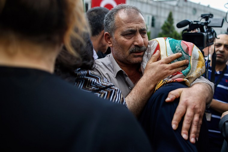 Family members of Erol Eskisoy and Ali Zulfikar Yorulmaz, two taxi drivers killed in Tuesday blasts, mourn during a memorial ceremony at the Ataturk Airport in Istanbul, Thursday, June 30, 2016. A senior Turkish official on Thursday identified the Istanbul airport attackers as a Russian, Uzbek and Kyrgyz national hours after police carried out sweeping raids across the city looking for Islamic State suspects. Tuesday's gunfire and suicide bombing attack at Ataturk Airport killed dozens and injured over 200. Turkish authorities have banned distribution of images relating to the Ataturk airport attack within Turkey. (AP Photo/Emrah Gurel)