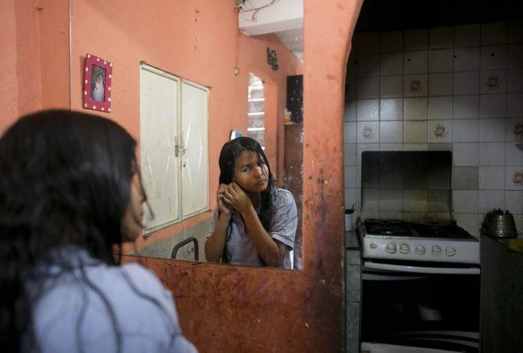 In this June 1, 2016 photo, Maria Arias stands near her kitchen as she puts on earrings while getting ready for school in Caracas, Venezuela. So many students have fainted from hunger at Maria's school that administrators told parents to keep their children home until they could find more food. (AP Photo/Ariana Cubillos)