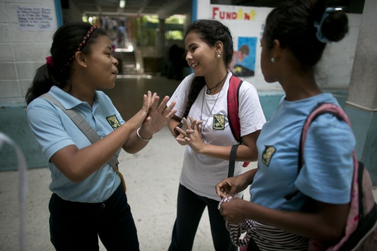 "In this May 31, 2016 photo, Maria Arias, center, shares a moment with classmates as they wait for their teacher to arrive for class at their public high school in Caracas, Venezuela. Arias lives in a violent neighborhood and has grown accustomed to her teachers not showing up for class. ""It's a trap,"" the 14 year-old complained. ""You risk your life to be here and end up waiting around for hours doing nothing. But you have to keep coming because it's the only way out."" (AP Photo/Ariana Cubillos)"
