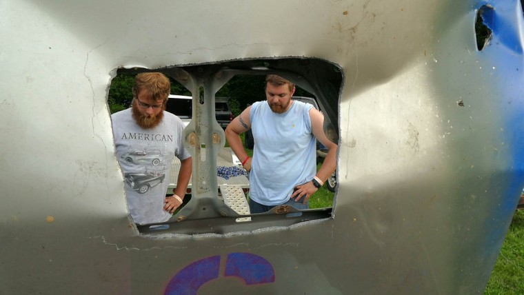 In a view through a hole in its hood, Michael Horchner (left) and Ryan Reid, both of Hagerstown hover in puzzlement over how to repair their Nissan Altima, which suffered damage in the engine compartment from multiple collisions of their recent race, during Demo Derby Day at Arcadia Volunteer Fire Company's carnival grounds. (Karl Merton Ferron/Baltimore Sun)