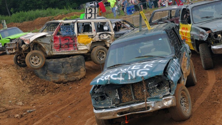 The heavy vehicles sit under a red flag during a spate of mayhem in which one SUV had flipped over and another - at left - backed itself over a tractor tire, waiting to be extracted during Demo Derby Day at Arcadia Volunteer Fire Company's carnival grounds. (Karl Merton Ferron/Baltimore Sun)