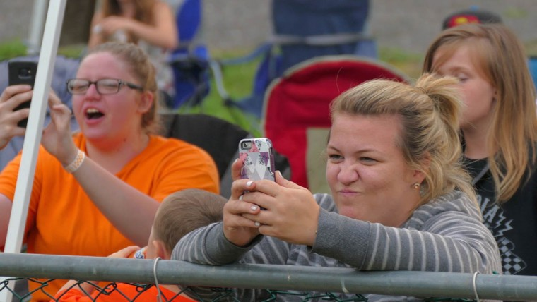 Heidi Brooks of Glen Burnie (right) captures video of the racing on her smart phone during Demo Derby Day at Arcadia Volunteer Fire Company's carnival grounds. (Karl Merton Ferron/Baltimore Sun)