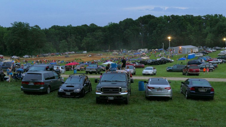 People use their vehicles like they would at a drive-in, enjoying the spectacle of car racing as dusk settles during Demo Derby Day at Arcadia Volunteer Fire Company's carnival grounds. (Karl Merton Ferron/Baltimore Sun)