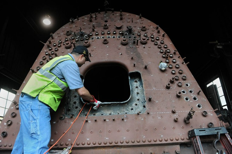 Jim Montague, fleet manager for the Western Maryland Scenic Railroad, looks into the fire box of the Chesapeake and Ohio Railroad No. 1309 steam locomotive. The train, which runs on coal, is being restored in the railroad's shop. When the restoration is complete, probably next year, the locomotive will pull passenger cars along the scenic railroad as it journeys between Cumberland and Frostburg. (Barbara Haddock Taylor, Baltimore Sun)