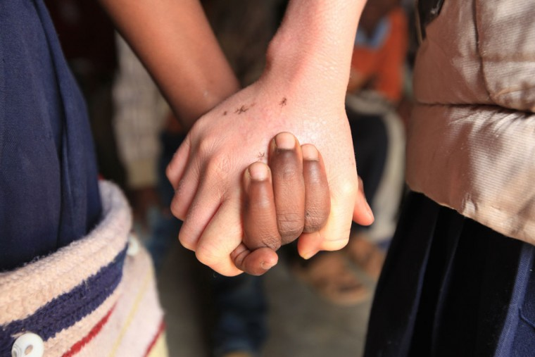 "Mina Godfrey, 13, right, holds hands with her best friend Charity Kamwendo at her school in this Tuesday, May, 24, 2016 photo in Machinga. Godfrey says she was placed first in her recent school exams and hopes one day to become a lawyer. But this comes after she survived abduction from her bed at night by her uncle. At least 18 Albino people have been killed in Malawi in a ""steep upsurge in killings"" since November 2014, and five others have been abducted and remain missing, a new Amnesty International report released Tuesday says. (AP Photo/Tsvangirayi Mukwazhi)"