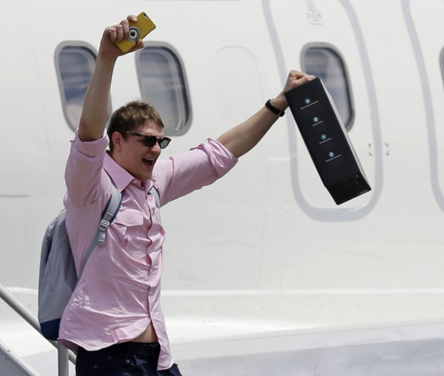 Cleveland Cavaliers' Timofey Mozgov, from Russia, raises his arms as he departs the airplane in Cleveland, Monday, June 20, 2016. The Cavaliers defeated Golden State in Game 7 of the NBA Finals on Sunday in Oakland, Calif. (AP Photo/Tony Dejak)