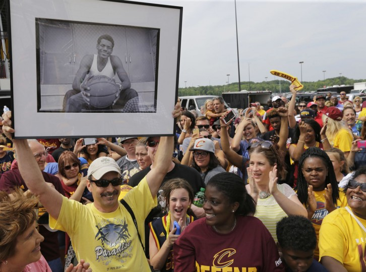A man holds up a photo of a young LeBron James while waiting for the NBA basketball Champion Cleveland Cavaliers to arrive in Cleveland, Monday, June 20, 2016. (AP Photo/Tony Dejak)