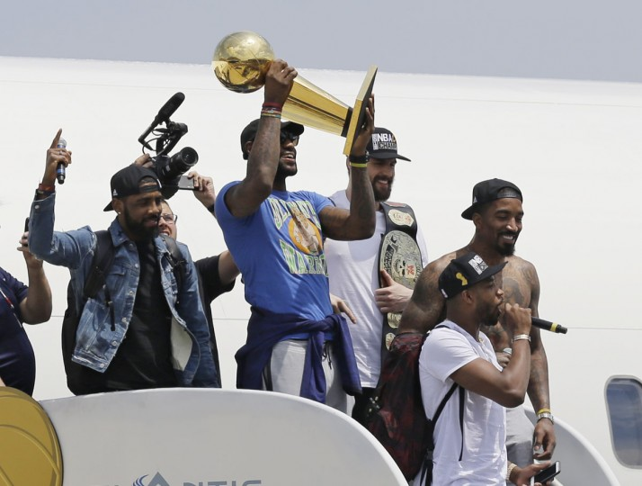 Cleveland Cavaliers' LeBron James holds up the NBA Championship trophy alongside teammates after arriving in Cleveland, Monday, June 20, 2016. (AP Photo/Tony Dejak)