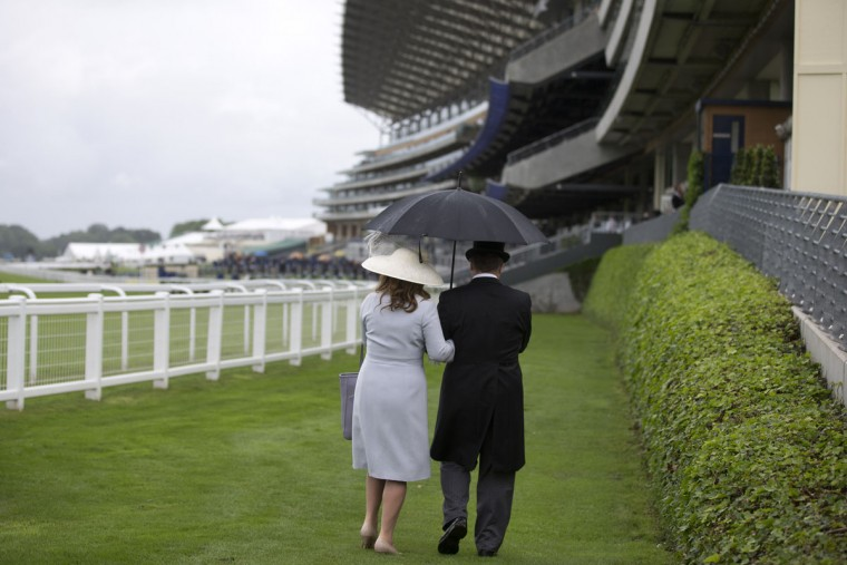 Racegoers shelter from the rain during a downpour on the first day of the Royal Ascot horse racing meet, in Ascot, west of London, on June 14, 2016. (JUSTIN TALLIS/AFP/Getty Images)