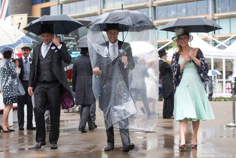 Racegoers shelter from the rain on the first day of the Royal Ascot horse racing meet in Ascot, west of London on June 14, 2016. (JUSTIN TALLIS/AFP/Getty Images)