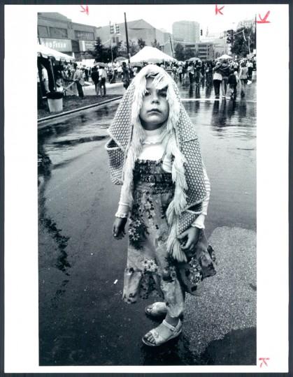 Samantha Corbin of Bolton Hill, uses make shift umbrella to brave the rain at the 1982 Artscape. June 13, 1982. (Smallwood/Baltimore Sun)
