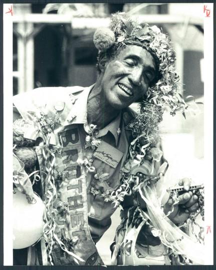 Festooned and beribboned, master storyteller Brother Blue a.k.a. Dr. Hugh Morgan Hill from Cambridge, Massachusetts entertains at Baltimore's second Artscape festival. 1983. (Phillips/Baltimore Sun)