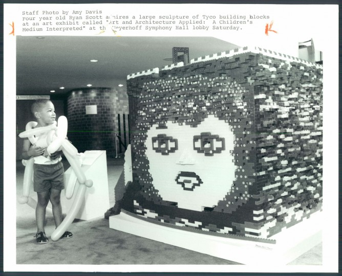 """Four year old Ryan Scott admires a large sculpture of Tyco building blocks at an art exhibit called """"Art and Architecture Applied; A Children's Medium Interpreted"""" at the Meyerhoff Symphony Hall lobby Saturday. 1988. (Davis/Baltimore Sun)"""