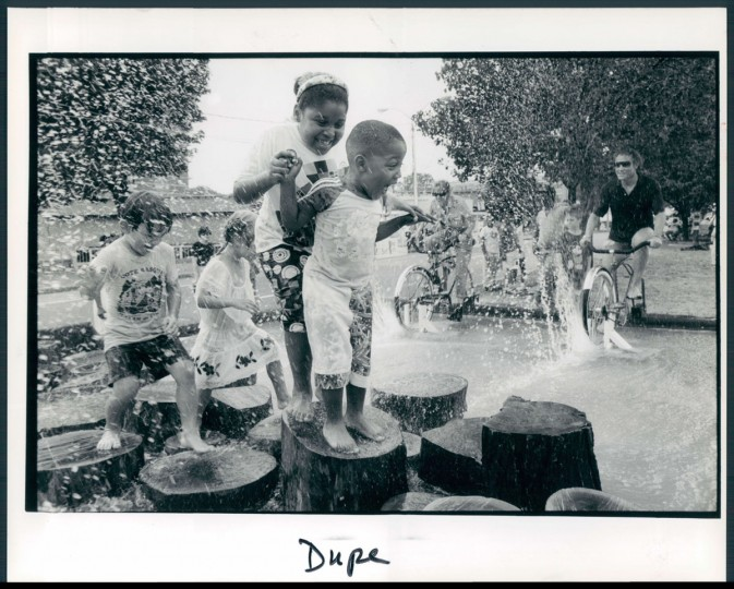 """July 18, 1992 - ARTSCAPE -- Laura Williams (8) and Antonio Brailsford (4) both of Baltimore stop on the """"Interactive Fountain"""" as they get splashes by cyclist, Louis Berney (right) at Artscape '92. Photo taken by Baltimore Sun Staff Photographer Mark Bugnaski."""
