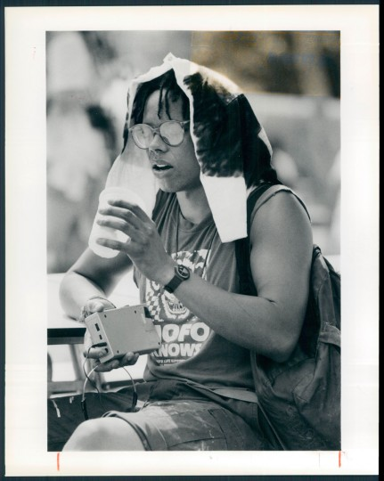 Steve Frazier copes with the heat at the Mount Royal Avenue's Artscape with a cold drink and a shirt draped over his head. 1988. (Davis/Baltimore Sun)
