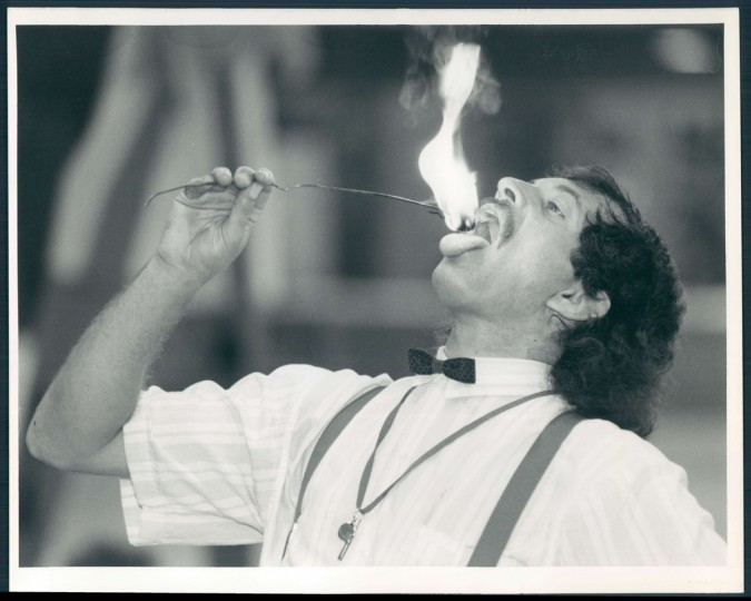 """Fire eater Stuart L. Buchwald aka """"Stuartini The Magnificent"""" pleases the crowd at Artscape held at the 5th Regiment Armory due to bad weather. 1989. (Thorsvik/Baltimore Sun)"""