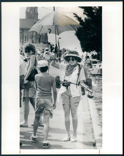 "Susan Sabatino, who entertained Artscape visitors as ""Libby Stone - Intrepid Explorer,"" had an umbrella and safari accoutrements to ward off the hot sun. 1988. (Davis/Baltimore Sun)"