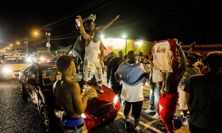 Protesters dance on the hood of a car as traffic backs up near the convenience store where Alton Sterling was shot and killed, July 6, 2016 in Baton Rouge, Louisiana. Sterling was shot by a police officer in front of the Triple S Food Mart in Baton Rouge on Tuesday, July 5, leading the Department of Justice to open a civil rights investigation. (Photo by Mark Wallheiser/Getty Images)