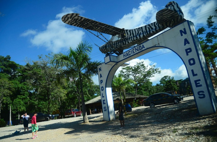 People pose for pictures at the entrance of the Hacienda Napoles theme park, once the private zoo of drug kingpin Pablo Escobar at his Napoles ranch, in Doradal, Antioquia department, Colombia on June 22, 2016. (RAUL ARBOLEDA/AFP/Getty Images)