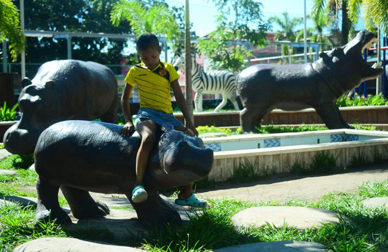 A boy sits on a hippo model at Jorge Tulio Garces neighborhood in Doradal, Antioquia department, Colombia, near the Hacienda Napoles theme park, once the private zoo of drug kingpin Pablo Escobar at his Napoles ranch, on June 22, 2016. (RAUL ARBOLEDA/AFP/Getty Images)