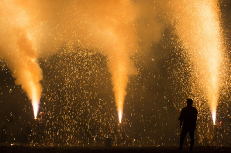 Pyrotechnicians hold bamboo cylinders containing fireworks as they perform 'tezutsu hanabi' or hand held fireworks at the Yoshida Shrine on July 15, 2016 in Toyohashi, Japan. The firework event was held as part of Toyohashi city's annual Gion Festival, which has 460 years history in the central Japanese region. (Photo by Tomohiro Ohsumi/Getty Images)