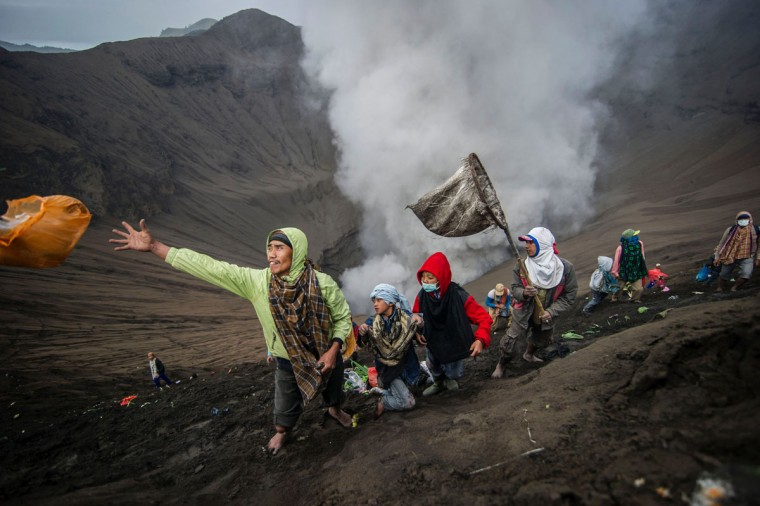 Villagers catch offerings released by Hindu devotees of the Tengger tribe during the Yadnya Kasada festival, on the crater of Mount Bromo in Probolinggo on July 21, 2016.During the annual Yadnya Kasada festival the Tenggerese climb Mount Bromo, an active volcano, and seek the blessing from the main deity Hyang Widi Wasa by presenting offerings of rice, fruit, livestock and other local produce. / (AFP Photo/Juni Kriswanto)