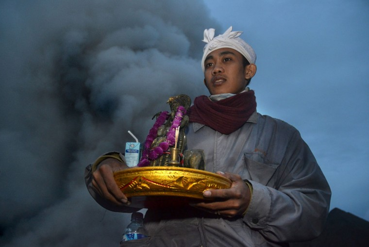 A Hindu priest from the Tengger tribe holds offerings during the Yadnya Kasada festival, on the crater of Mount Bromo in Probolinggo on July 21, 2016. During the annual Yadnya Kasada festival the Tenggerese climb Mount Bromo, an active volcano, and seek the blessing from the main deity Hyang Widi Wasa by presenting offerings of rice, fruit, livestock and other local produce. / (AFP Photo/Aman Rochman)