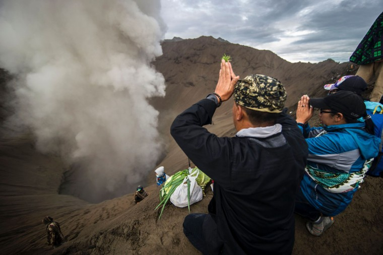 Hindu devotees of the Tengger tribe pray during the Yadnya Kasada festival, on the crater of Mount Bromo in Probolinggo on July 21, 2016. During the annual Yadnya Kasada festival the Tenggerese climb Mount Bromo, an active volcano, and seek the blessing from the main deity Hyang Widi Wasa by presenting offerings of rice, fruit, livestock and other local produce. / (AFP Photo/Juni Kriswanto)