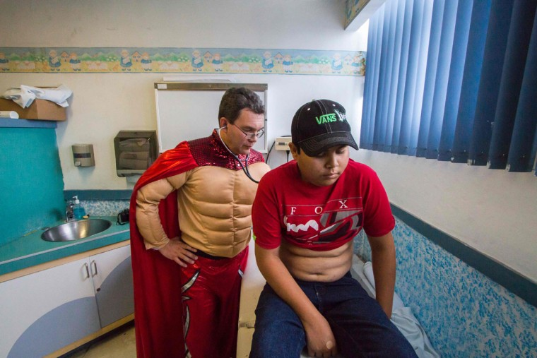 Mexican pediatric oncologist Sergio Gallegos, disguised as a traditional Mexican wrestler, checks a patient at a hospital in Guadalajara, Mexico on July 12, 2016. Gallegos believes the mood of his patients is very important for the success of cancer treatment, so he disguises as different characters. (HECTOR GUERRERO/AFP/Getty Images)