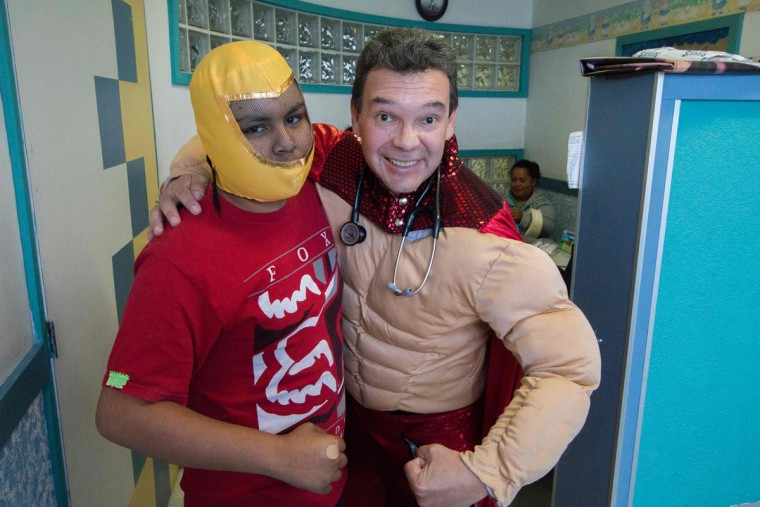Mexican pediatric oncologist Sergio Gallegos, disguised as a traditional Mexican wrestler, poses with a patient at a hospital in Guadalajara, Mexico on July 12, 2016. Gallegos believes the mood of his patients is very important for the success of cancer treatment, so he disguises as different characters. (HECTOR GUERRERO/AFP/Getty Images)