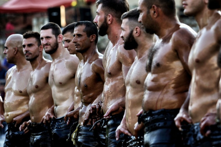 Athletes stand before taking part in a competition of oil wrestling in Sohos, a village north of Thessaloniki on June 30, 2016. (SAKIS MITROLIDIS/AFP/Getty Images)