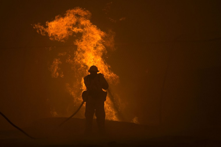 A firefighter hoses down burning pipes near a water tank at the Sand Fire on July 23 2016 near Santa Clarita, California. Fueled by temperatures reaching about 108 degrees fahrenheit, the wildfire began yesterday has grown to 11,000 acres. (AFP PHOTO / DAVID MCNEW)