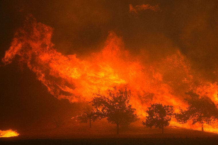 Flames blown by strong winds close in on homes at the Sand Fire on July 23 2016 near Santa Clarita, California. Fueled by temperatures reaching about 108 degrees fahrenheit, the wildfire began yesterday has grown to 11,000 acres. (AFP PHOTO / DAVID MCNEW)