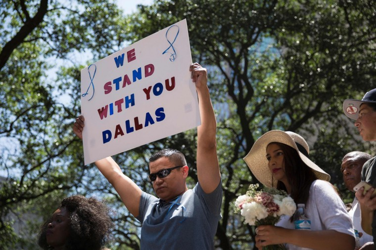 """A man holds a sign reading """"We Stand With You Dallas"""" during a vigil at Thanks-Giving Square in Dallas, Texas, on July 8, 2016, following the shootings during a peaceful protest on July 7 which left 5 police officers dead. (Laura Buckman/AFP/Getty Images)"""