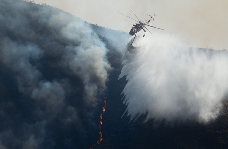 A helicopter drops water on the Soberane Fire in Carmel Highlands, California on July 23, 2016. The fire has scored more than 10,000 acres and threatens 1,650 structures according to Cal Fire. (AFP PHOTO / NOAH BERGER)