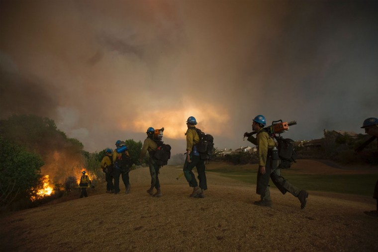 Firefighters of the Texas Canyon Hotshot crew fight the Sand Fire at a residential golf course on July 23 2016 near Santa Clarita, California. Fueled by temperatures reaching about 108 degrees fahrenheit, the wildfire began yesterday has grown to 11,000 acres. (AFP PHOTO / DAVID MCNEW)