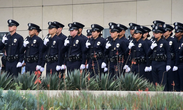 With black ribbons across their badge and holding a gun, police recruits attend their graduation ceremony at LAPD Headquarters where rappers Snoop Dogg and The Game led a peaceful demonstration outside on July 8, 2016 in Los Angeles, California, in what they called an effort to promote unity in the aftermath of the deadly shootings of police officers in Dallas. (Frederic J. Brown/AFP/Getty Images)