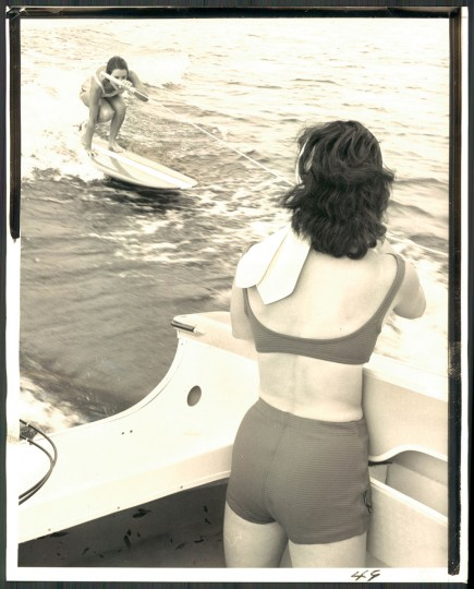 """""""Once the surfer is upright, she adjusts her feet on the board to maneuver it into the right position on the face of wake."""" July 6, 1964. (Baltimore Sun)"""