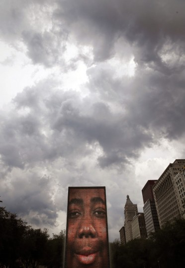 Storm clouds roll above the Crown Fountain in Chicago's Millennium Park bringing temporary relief to the Midwest's excessive heat Thursday, July 21, 2016, in Chicago. The fountain is an interactive work of public art and video sculpture. (AP Photo/Charles Rex Arbogast)