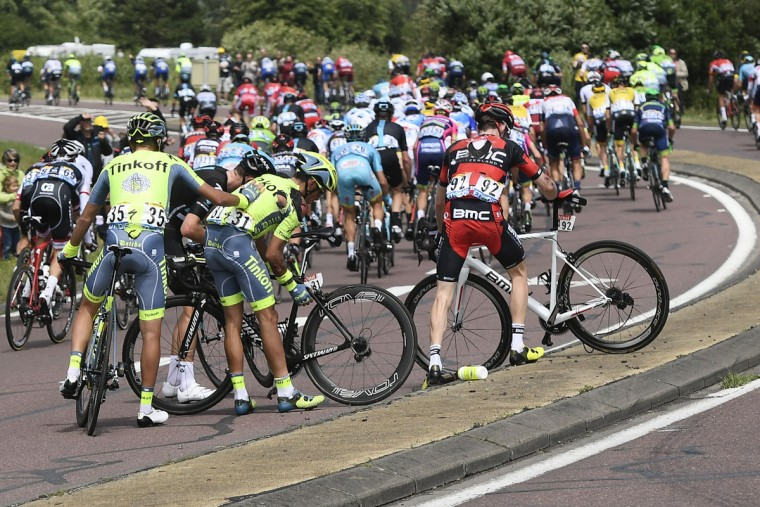 Croatiaís Robert Kiserlovski, left, helps his team leader Spain's Alberto Contador, second left, after he crashed with Brent Bookwalter of the U.S., right, during the first stage of the Tour de France cycling race over 188 kilometers (116.8 miles) with start in Mont-Saint-Michel and finish in Utah Beach, France, Saturday, July 2, 2016. (Jerome Prevost, Pool via AP)