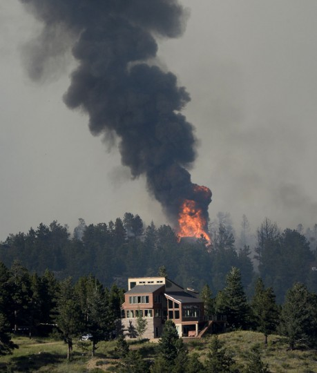 A fire burns behind a house during the Cold Springs Nederland fire in Colorado on Saturday July 9, 2016. (Paul Aiken/Boulder Daily Camera via AP)