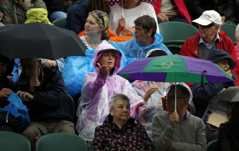 Spectators take shelter from the rain during day five of the Wimbledon Tennis Championships in London, Friday, July 1, 2016. (AP Photo/Alastair Grant)