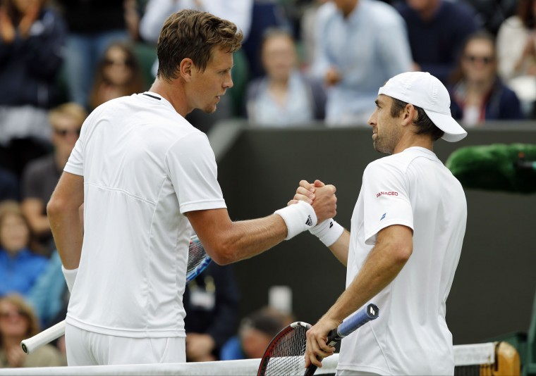 Tomas Berdych of the Czech Republic, left, shakes hands with Benjamin Becker of Germany after beating him in their men's singles match on day five of the Wimbledon Tennis Championships in London, Friday, July 1, 2016. (AP Photo/Alastair Grant)