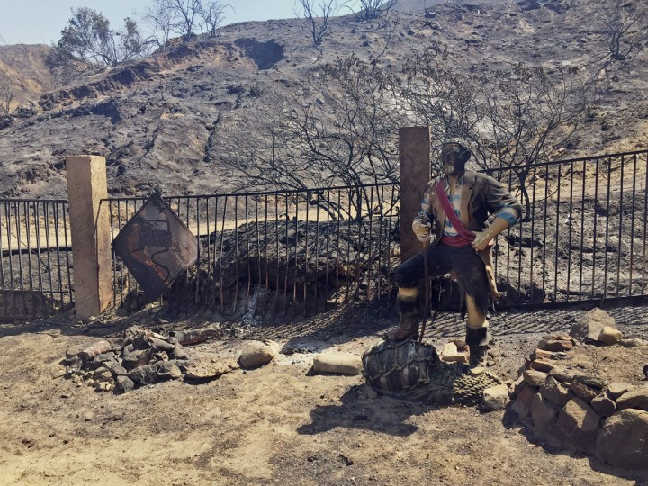 A burned pirate sculpture stands at the end of Iron Canyon Road off of Sand Canyon in Santa Clarita, Calif., on Sunday, July 24, 2016. Two massive wildfires raged in tinder-dry California hills and canyons Sunday, leaving thousands of homes evacuated and authorities to investigate a burned body found in a neighborhood swept by flames. Firefighters have been trying to beat back a fire since Friday that has blackened more than 34 square miles of brush on ridgelines near the city of Santa Clarita and the Angeles National Forest. (AP Photo/Matt Hartman)