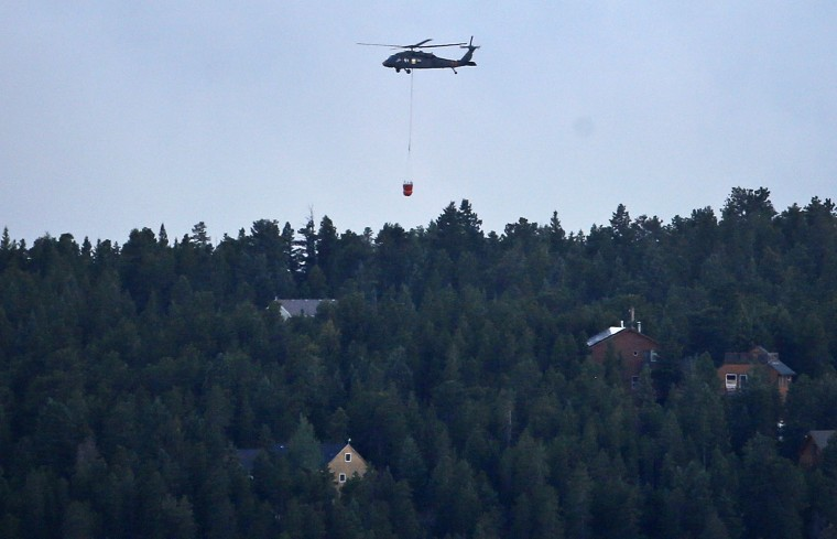 A military Blackhawk helicopter carries a water bucket while battling the Cold Springs Fire near Nederland, as viewed from Sugarloaf, Colo. on Sunday, July 10, 2016. Fire authorities are warning that shifting high winds and high temperatures could put homes in danger. The fire that started on Saturday spread quickly. (AP Photo/Brennan Linsley)