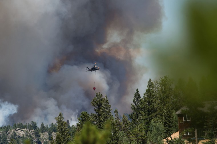 A helicopter prepares to drop water on a wildfire fire in Nederland, Colo., Sunday, July 10, 2016. (Autumn Parry/Daily Camera via AP)